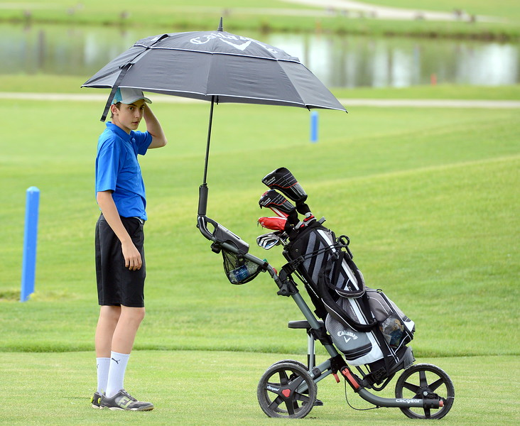 Adrian Tabin spins the umbrella on his cart during the Junior Optimist golf tournament Monday at the Olde Course in Loveland. (Mike Brohard/Loveland Reporter-Herald)