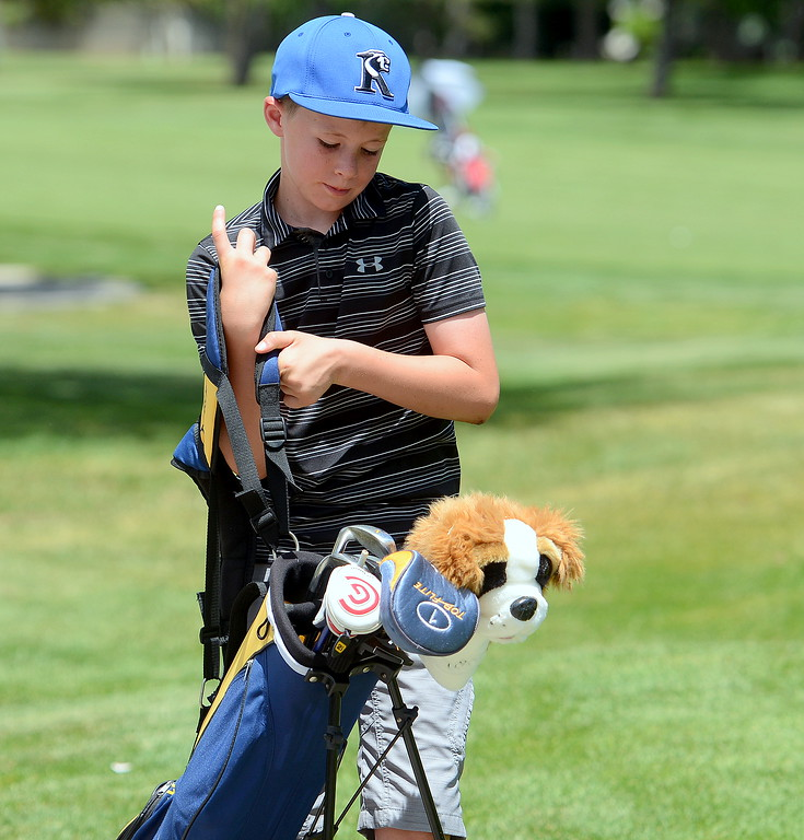 . Graham Riggs picks up his clubs and heads to his next shot during the Junior Optimist golf tournament Monday at the Olde Course in Loveland. (Mike Brohard/Loveland Reporter-Herald)