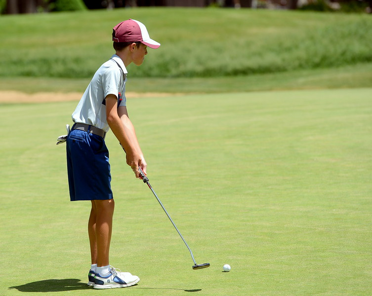 Austin Barry takes a few practice swings as he reads the green on the third hole during the Junior Optimist golf tournament Monday at the Olde Course in Loveland. (Mike Brohard/Loveland Reporter-Herald)