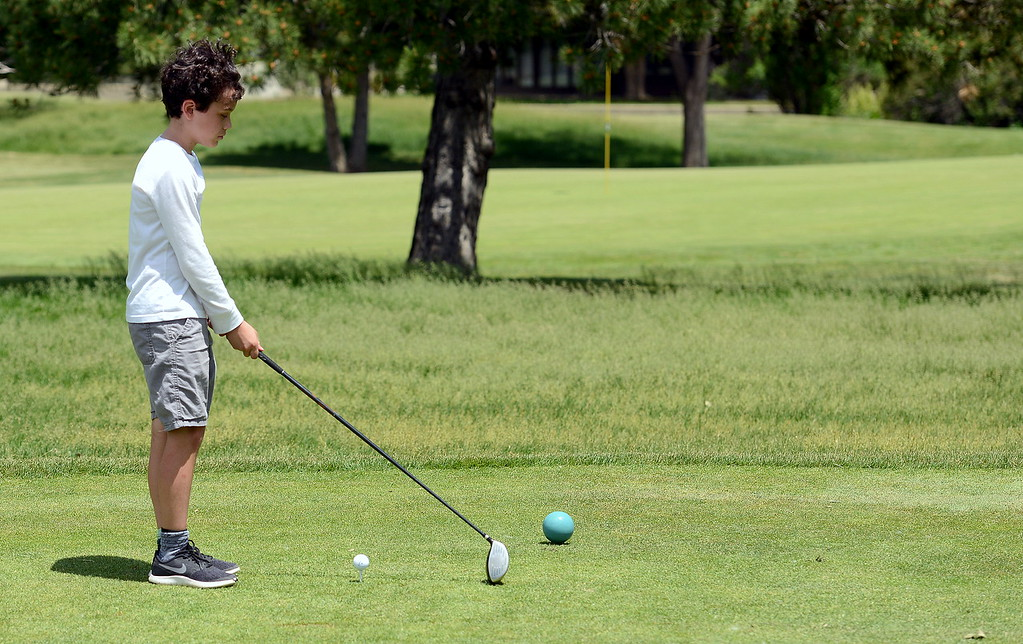. Mason Ramirez finds his line as he prepares to drive during the Junior Optimist golf tournament Monday at the Olde Course in Loveland. (Mike Brohard/Loveland Reporter-Herald)