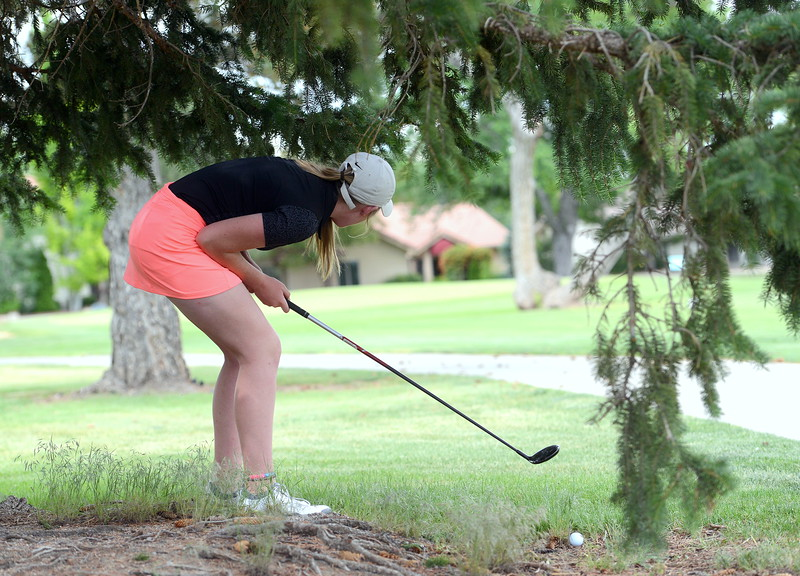 Taylor Bandemer ducks down to find a line she likes after hitting under a tree on No. 10 during the Junior Optimist golf tournament Monday at the Olde Course in Loveland. She won the girls 15-18 title with an 80, earning a paid trip to the district round. (Mike Brohard/Loveland Reporter-Herald)