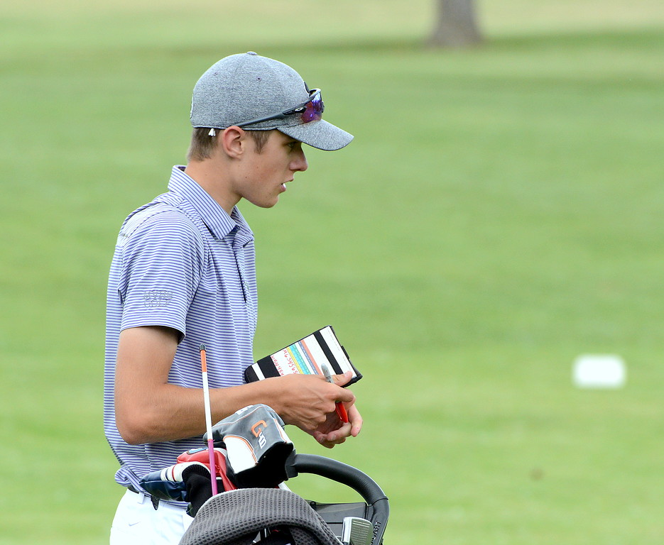 . Wes Weber marks down his score after hitting a clutch putt on No. 16 during the Junior Optimist golf tournament Monday at the Olde Course in Loveland. (Mike Brohard/Loveland Reporter-Herald)