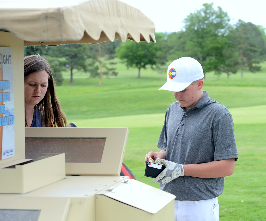 . Austin Percha buys some water from Natialie Link during the Junior Optimist golf tournament Monday at the Olde Course in Loveland. Temperatures hit the 90s during the round. (Mike Brohard/Loveland Reporter-Herald)