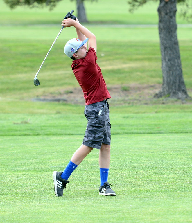 . Charlie Riggs follows through with his shot during the Junior Optimist golf tournament Monday at the Olde Course in Loveland. (Mike Brohard/Loveland Reporter-Herald)