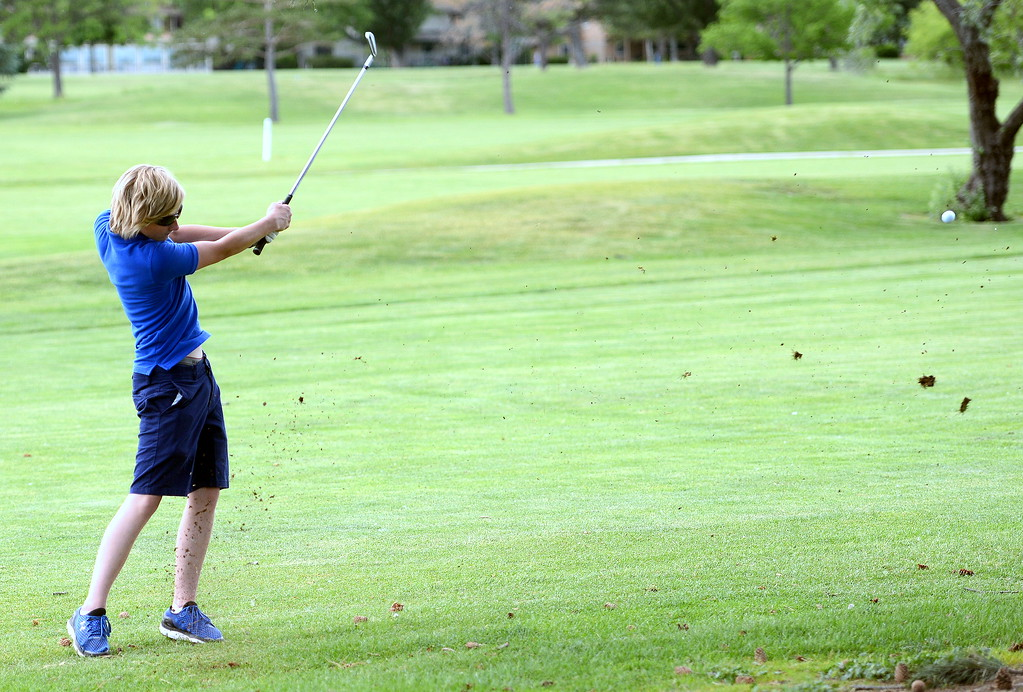 . Taylor Dubois hits an iron during the Junior Optimist golf tournament Monday at the Olde Course in Loveland. (Mike Brohard/Loveland Reporter-Herald)