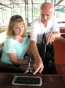 "Charles Mistele, right, shows Kirsten Johnson some of the dings and dents that Miss America IX  accumulated during her racing days. ""This boat was made for racing, not to look pretty,"" said Mistele of the marks, most of which have been left without repair. Johnson is a great-niece of Gar Wood, and is researching her family history, prompting a meeting with Mistele during the ACBS Blue Ridge Chapter's 27th Lake Chatuge Rendezvous in Hiawassee, GA."