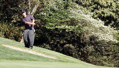 David Duval pitches from a hillside lie near the tenth green during the Wednesday Practice Day at the 2010 Masters at Augusta National Golf Club.