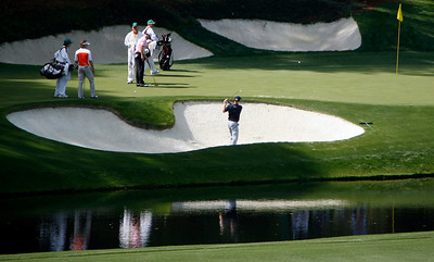A player pitches his ball from a greenside bunker on front of the twelfth green during the Wednesday Practice Day at the 2010 Masters at Augusta National Golf Club.
