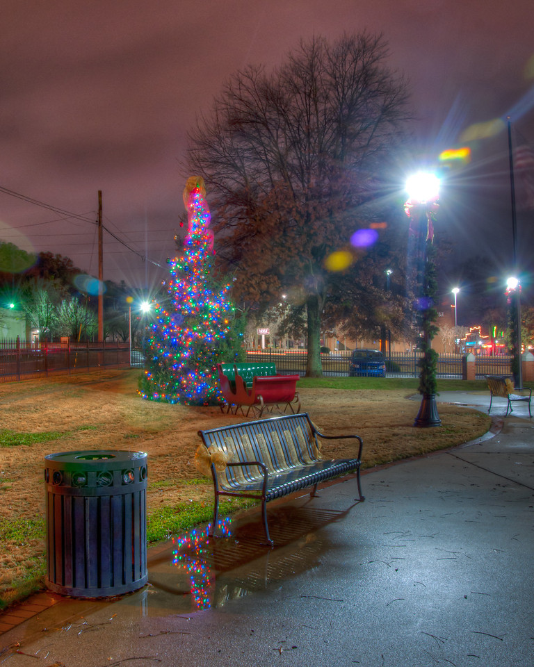 """<h3 style=""""text-align: left;""""><strong>Today's Photo:  Calhoun Christmas Tree</strong></h3> Downtown Calhoun Georgia is not a very big place.  In fact, if you blink, you may miss it.  I have driven through several times, and each time, I notice something I did not the time before.  This shot was of the Christmas Tree in the small park on the north side of town.  The park was not very large, maybe an acre and a half, but packed full of good compositions with the Christmas lights.  It had been raining most of the day and there were several puddles around.  Fortunately, this one was in just the right spot.  - Daryl Clark  Read more at the <a href=""""http://justshootingmemories.com"""">Daily Photography Blog</a> Just Shooting Memories!..."""