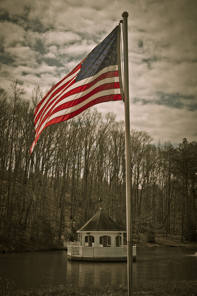 """<h3 style=""""text-align: left;""""><strong>Today's Photo: Flying Proud</strong></h3> It was a little windy the other day and I saw the flag flapping gently in the breeze.  I could not help but take a few shots.  I have been getting away from HDR lately and this is one of those that I processed without it.  Nothing like expanding the abilities."""