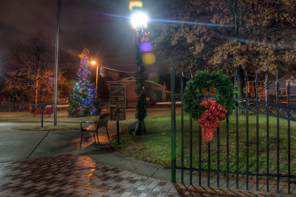 """<h3 style=""""text-align: left;""""><strong>Today's Photo:  The City Park</strong></h3> I was taking photos of the Christmas lights in Calhoun when I saw this wreath on the gate to the park.  I noticed it because my sister was taking photos in the same area, probably of the same thing.  It looked good against the Christmas tree and there was just enough light from the lamps behind me to balance the scene.  - Daryl Clark  Read more at the <a href=""""http://justshootingmemories.com"""">Daily Photography Blog</a> Just Shooting Memories!..."""