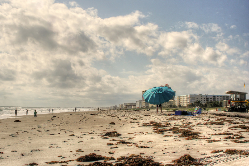 """<h3 style=""""text-align: left;""""><strong>Today's Photo:  Cocoa Beach</strong></h3> When I was a little, I went on a family vacation to Disney World in Orlando.  I remember that part of that vacation, we went to see Cape Canaveral.  I don't remember if we went to the beach while we were there.  Several years ago, I was in that area and decided to stop by Cocoa Beach for a little while.  It was cold and windy, but there were people all along the beach.  I found this one brave sole setting up an umbrella.  - Daryl Clark  Read more at the <a href=""""http://justshootingmemories.com"""">Daily Photography Blog</a> Just Shooting Memories!..."""
