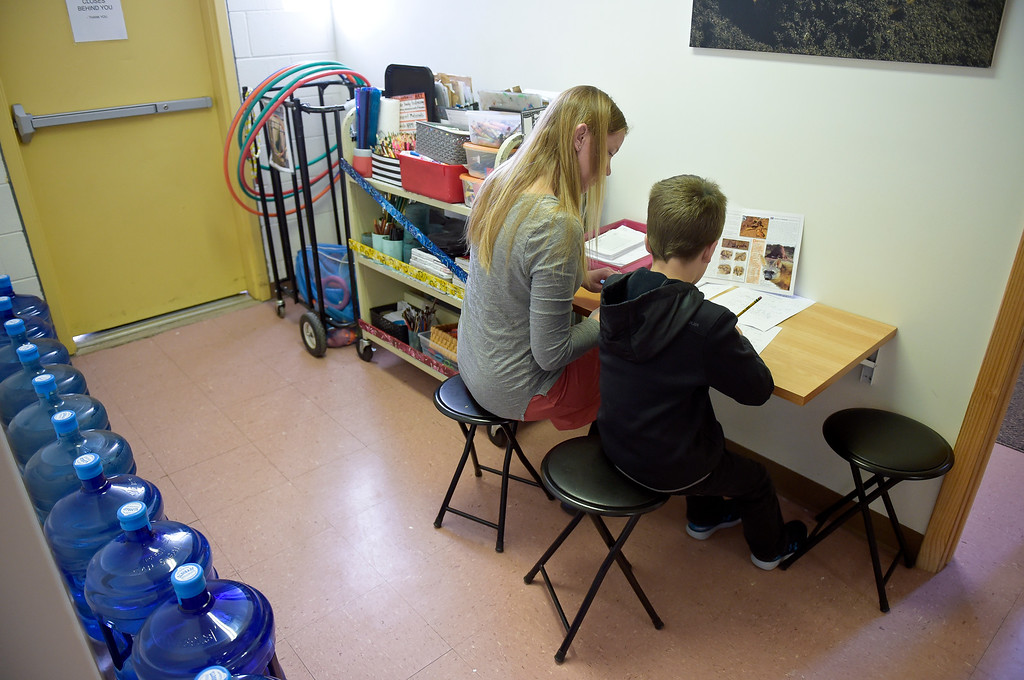 . LONGMONT, CO - MARCH 21: Paraeducator Nicole Lee works with a student in a lower elementary hallway at St. Vrain Community Montessori March 21, 2019. To view more photos visit timescall.com. (Photo by Lewis Geyer/Staff Photographer)  ***Student\'s face/ID not available for publication***