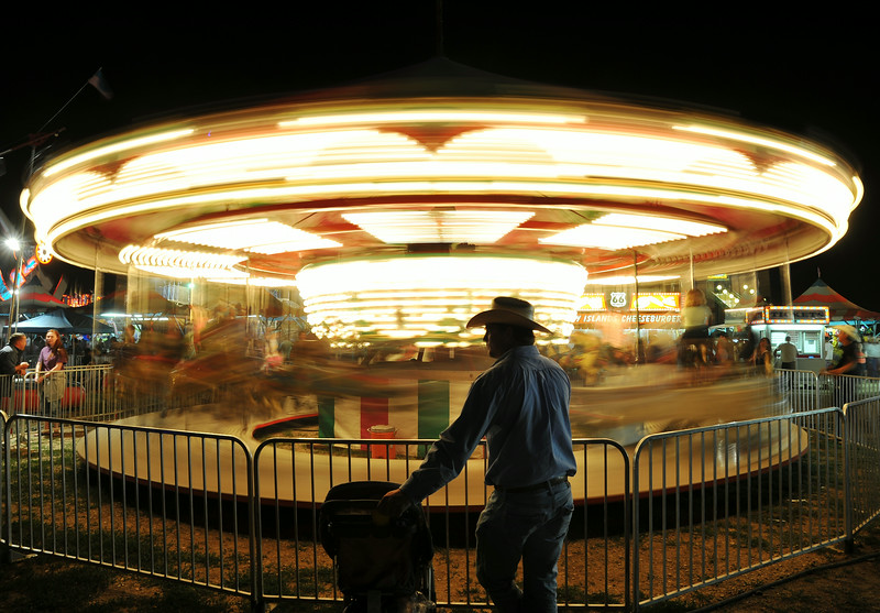 Cody Wright of Corsica, South Dakota, waits for his family as they ride the carousel in the carnival Saturday night at the Sheridan County Fairgrounds. The Sheridan Press|Justin Sheely.