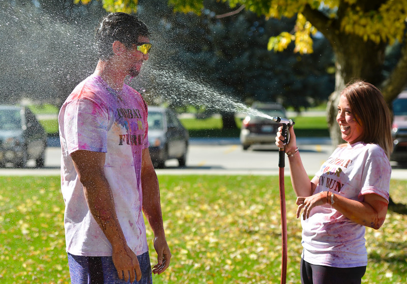Justin Sheely | The Sheridan Press<br /> Ian Scofield receives more than he bargained for as Alison Wigglesworth rinses off powder color during the 5th annual Combat Color Run last October at Sheridan College. The event was hosted by and benefits the Student Veterans of America at Sheridan College.