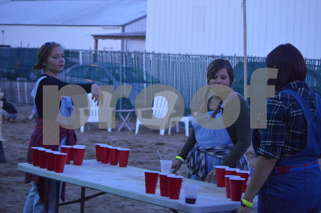 Tauni Sundermeyer, Miranda Engeldinger, and Megan Simpson play a game of pong outside the bar.