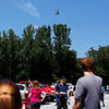 Workers take pictures and video of the KMAX helicopter as it passes over the parking lot of Kaman Composites.