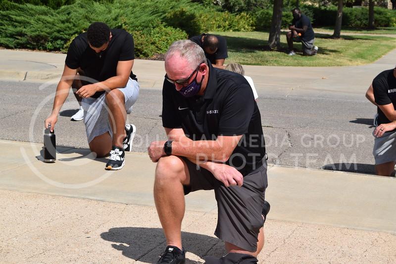 K-State Athletic Director Gene Taylor kneels during the K-State Athletics Walk Against Injustice on August 30, 2020. (Cameron Bradley | Collegian Media Group)