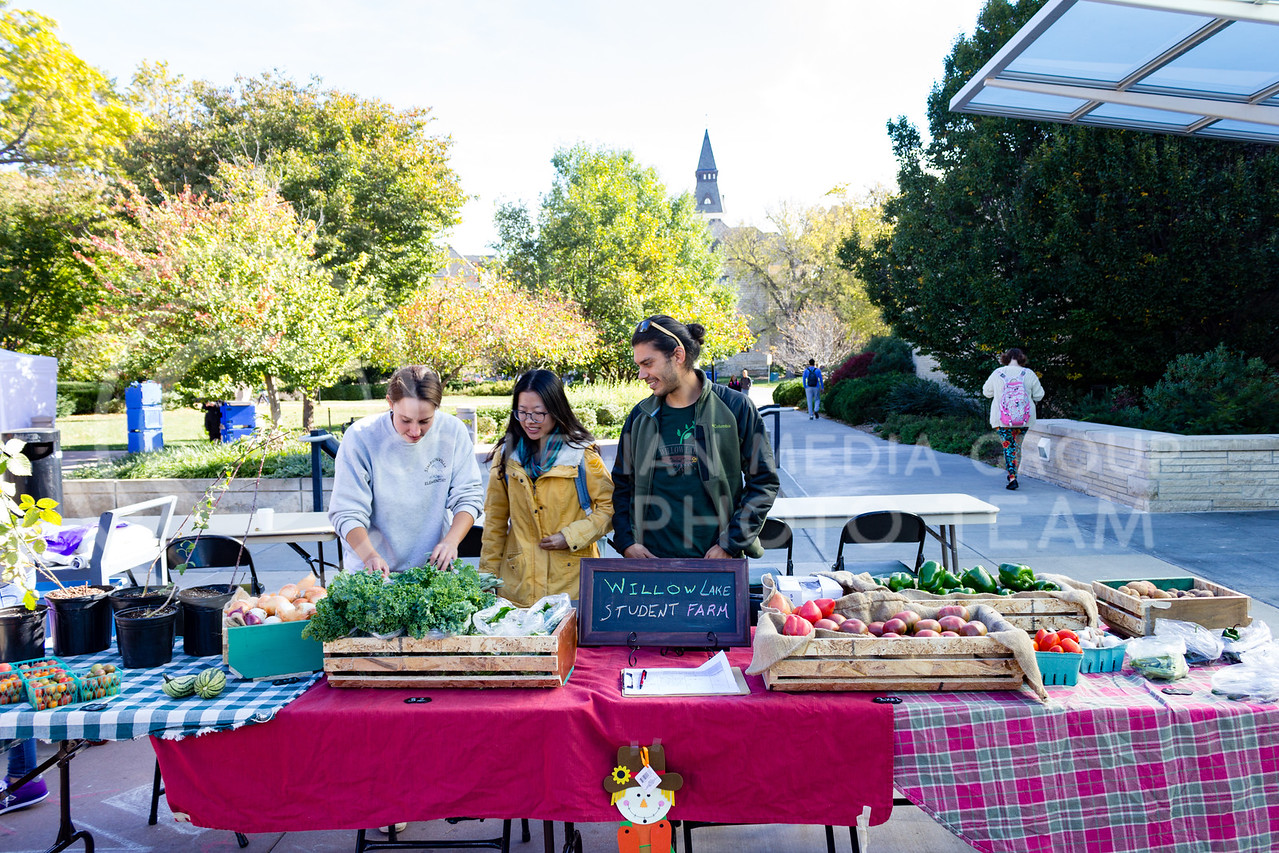 Erin Bailey, Huan Guo, and Kenny Artivia Set up the Willow Lake Student Farm table at the K-State Farmers Market on 25th October, 2017 (Alex Shaw | Collegian Media Group)