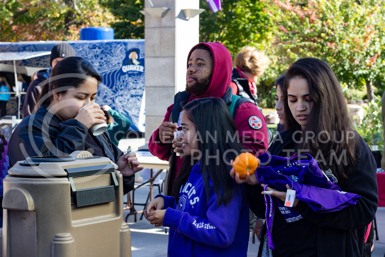 Students make apple cider and pick up free gifts at the UPC table at the K-State Farmers Market on the 25th October, 2017 (Alex Shaw | Collegian Media Group)
