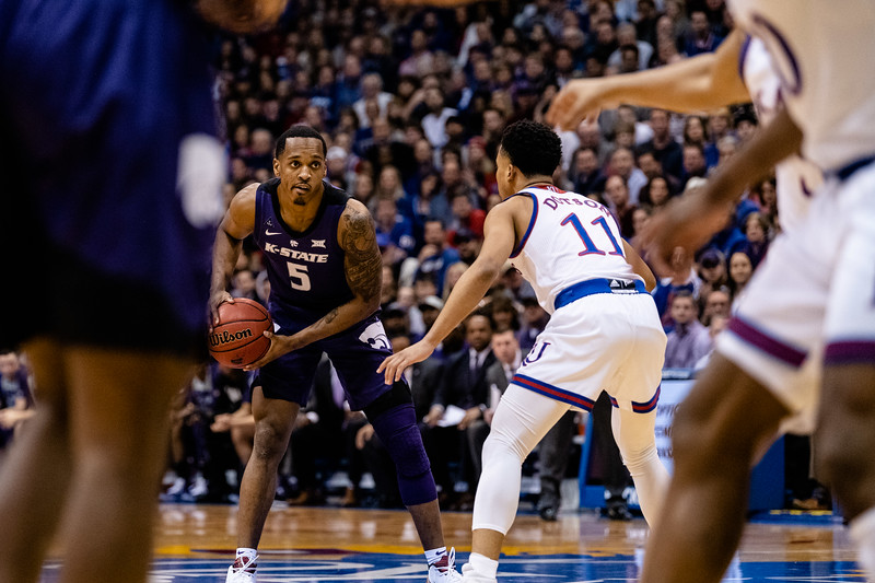 K-State Wildcat senior guard Barry Brown Jr. looks towards the baseline for an opening while Jayhawk freshman guard Devon Dotson defends her. The Kansas State Wildcats played against the Kansas Jayhawks at Allen Fieldhouse on Monday Feb. 26, 2019 losing 64-49. (Olivia Bergmeier | Collegian Media Group)