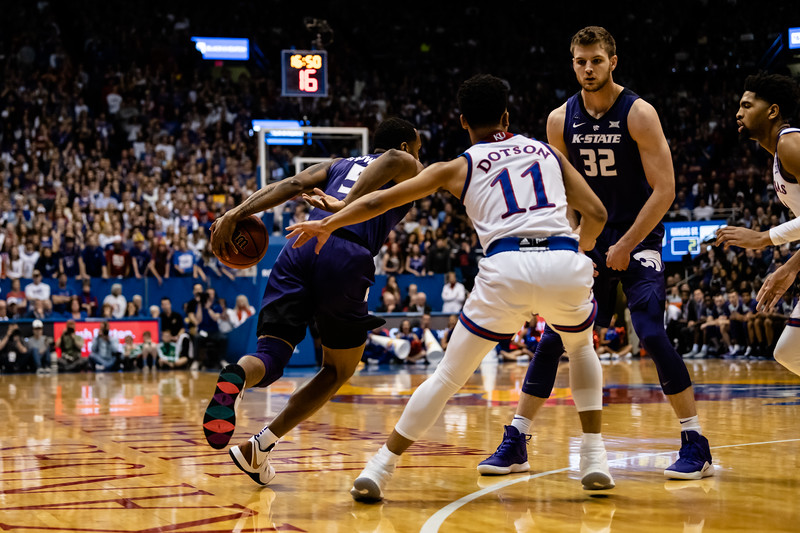 K-State Wildcat senior guard Barry Brown Jr. runs past Jayhawk freshman guard Devon Dotson and Wildcat senior forward Dean Wade as helooks to the opposite side of the court for an opening. The Kansas State Wildcats played against the Kansas Jayhawks at Allen Fieldhouse on Monday Feb. 26, 2019 losing 64-49. (Olivia Bergmeier | Collegian Media Group)