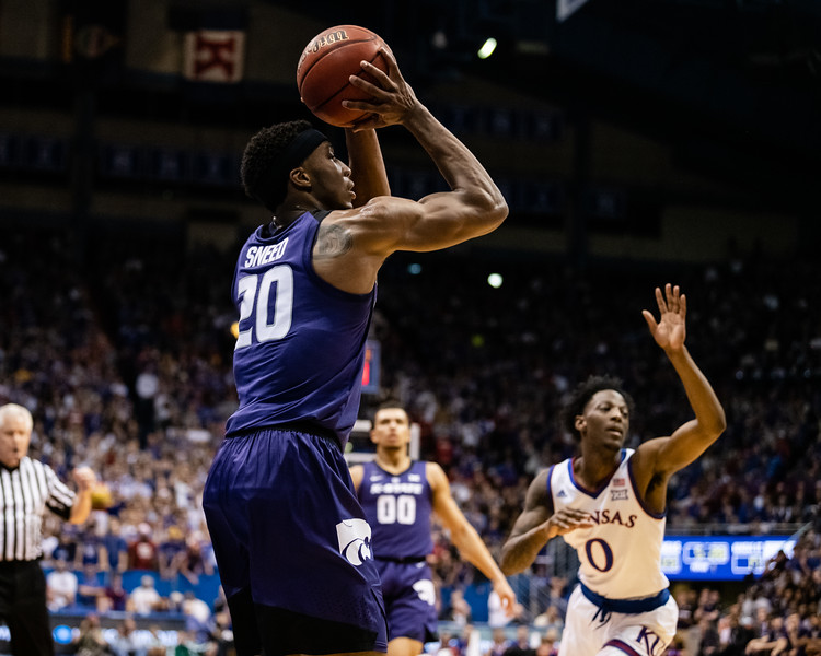 K-State Wildcat junior forward Xavier Sneed shoots for three while Jayhawk sophomore guard Marcus Garrett and other defenders rush to block him. The Kansas State Wildcats played against the Kansas Jayhawks at Allen Fieldhouse on Monday Feb. 26, 2019 losing 64-49. (Olivia Bergmeier | Collegian Media Group)