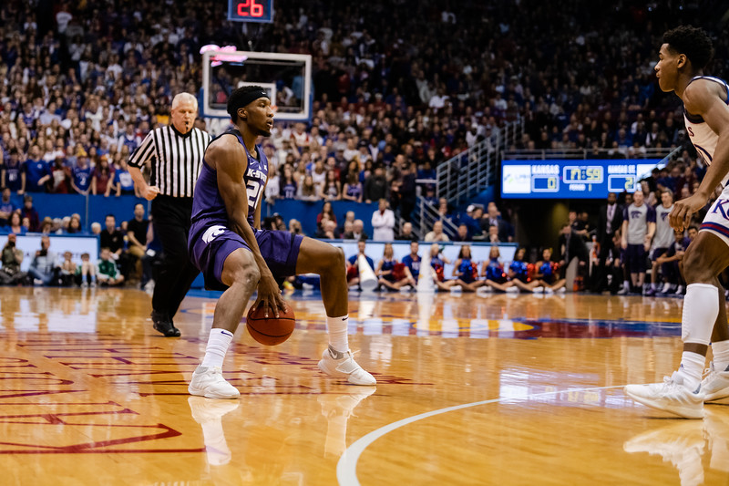 K-State Wildcat junior forward Xavier Sneed dribbles the ball between his legs as he sets up the next play. The Kansas State Wildcats played against the Kansas Jayhawks at Allen Fieldhouse on Monday Feb. 26, 2019 losing 64-49. (Olivia Bergmeier | Collegian Media Group)