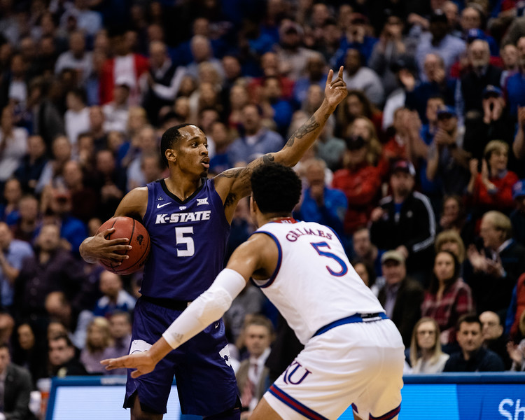 K-State Wildcat senior guard talks with his teammates while Jayhawk freshman guard Quenton Grimes defends him. The Kansas State Wildcats played against the Kansas Jayhawks at Allen Fieldhouse on Monday Feb. 26, 2019 losing 64-49. (Olivia Bergmeier | Collegian Media Group)