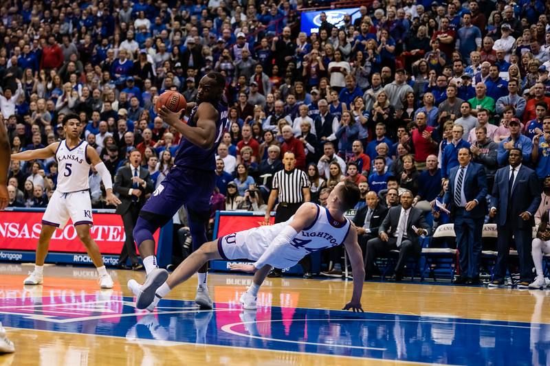 K-State Wildcat junior forward Makol Mawien spins to look for the basket as Kansas Jayhawk junior forward Mithc Lightfoot falls to the floor. The K-State Wildcats fell to the Kansas Jayhawks in Allen Fieldhouse 64-49. (Olivia Bergmeier | Collegian Media Group)