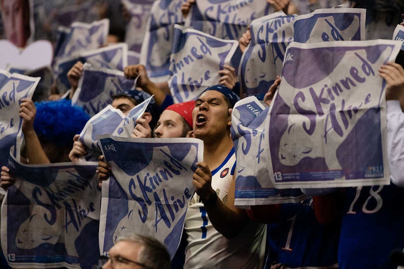A University of Kansas student cheers in the student section while shaking a copy of the University Daily Kansan newspaper. The Kansas State Wildcats played against the Kansas Jayhawks at Allen Fieldhouse on Monday Feb. 26, 2019 losing 64-49. (Olivia Bergmeier | Collegian Media Group)
