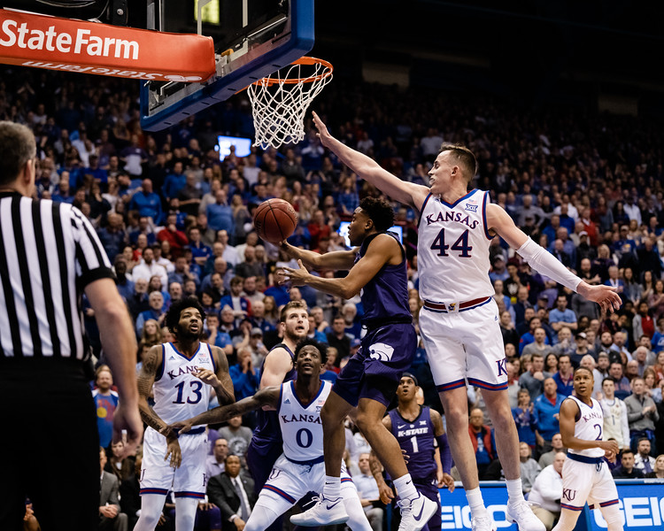 K-State Wildcat senior guard Kamau Stokes shoots a layup underneath the towering Jayhawk junior forward Mitch Lightfoot in attempt to score. The Kansas State Wildcats played against the Kansas Jayhawks at Allen Fieldhouse on Monday Feb. 26, 2019 losing 64-49. (Olivia Bergmeier | Collegian Media Group)