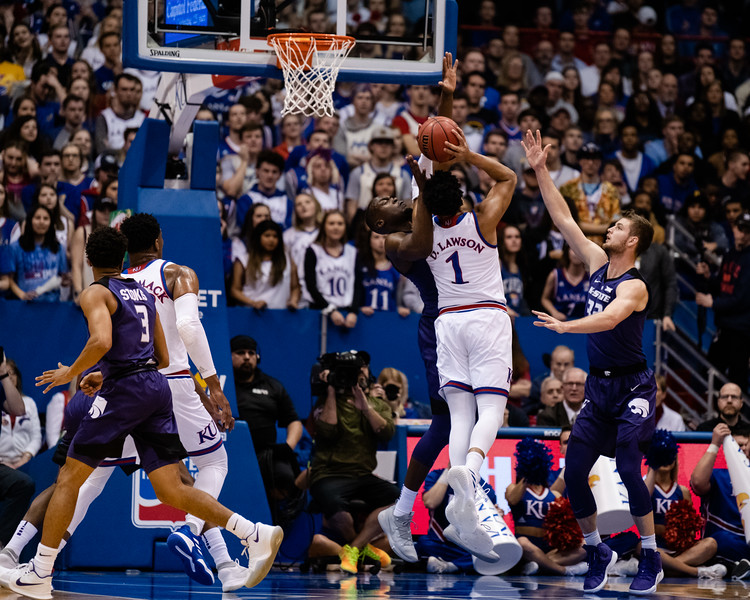 K-State wildcat junior forward Makol Mawien attempts to block Jayhawk junior forward Dedric Lawson from shooting the ball while Wildcat senior forward Dean Wade attempts to assist. The Kansas State Wildcats played against the Kansas Jayhawks at Allen Fieldhouse on Monday Feb. 26, 2019 losing 64-49. (Olivia Bergmeier | Collegian Media Group)
