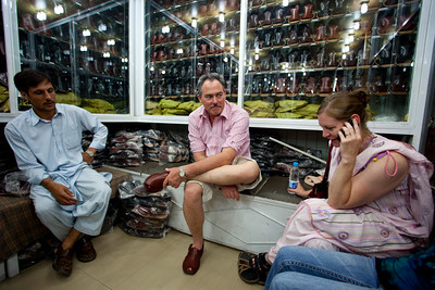 Shopping for Peshawari Chappals.   Here Linda is calling Rich to find out if he wants black or brown.  Meanwhile Matthew tries out his pair.