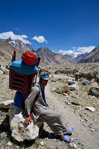 A porter rests with his load of plastic chairs for a different expedition.