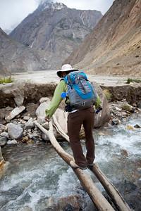 Linda carefully balances across a few trees across an icy mountain stream on the way to Sam Tsok.