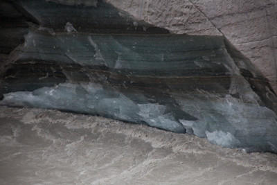 The mouth of the glacier.  The layers are the snowfalls that have been compacted so you can figure out the history of the glacier by the cross section.