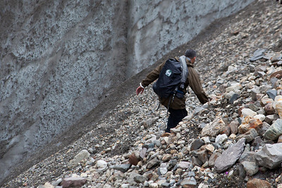 Adil navigates a trail above another sheared section of the glacier with a steep fall to the left.