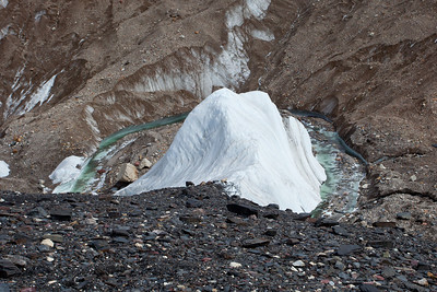 An emrald green river on the glacier as it skirts around an ice pyramid.  The scale is misleading.