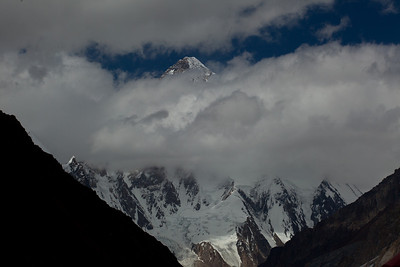 Still wrapped in gauzy cloak, we catch glimpses of K2's peak above the clouds.  Normally your eye does not even go up that high because it is in the clouds so it always came as s surprise to me to see ground way up there where it had no business!