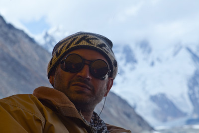 Adil's face lit up in the mess tent by reflected light with K2 in the background.