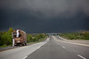 Monsoon clouds force the truckers to pull up the tarpaulins.