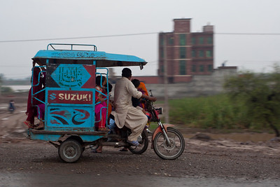 The peculiar Lahori rickshaw.  The newer version has a motorbike in front.  Usually itis a scooter.