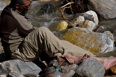 Adil tries to care for his battered, hamburger feet in the cold stream at Jula.  Rich had been doing a good job taking care of everyone's feet, but despite his best effort, Adil's feet were just too delicate.