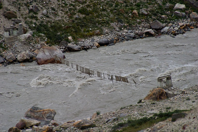 A bridge in disrepair across the Braldu river, likely taken out during a time of flooding.