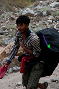 Ibrahim brings some of the bags across the gap.
