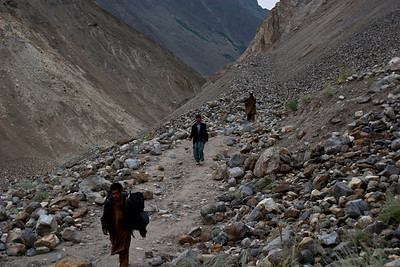 The porters bring bags across the break in the road.  They took the same lower path we had used on the way up.  Apparently unphased by it and unwilling to take the longer higher path with all the bags.