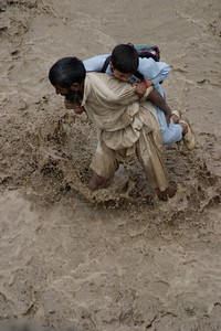 One of the porters carries across a boy on his way to school whose way is blocked by the break in the road.