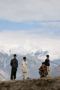 A number of locals watch with the mountains in backdrop.