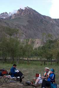 People settling down in camp, reading, and writing in their journals about the day's events.